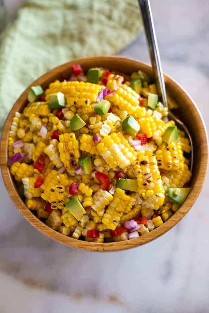 Corn salad made with grilled sweet corn, diced avocado, bell pepper and onion served in a wooden bowl with a spoon.