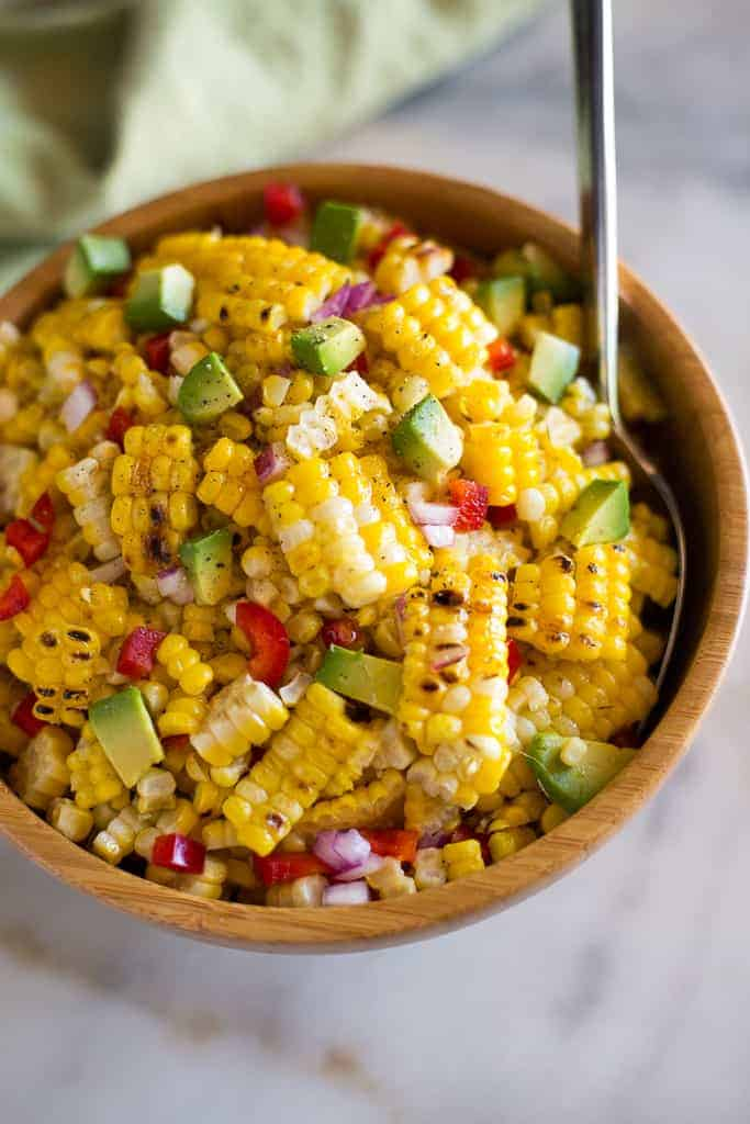A wooden bowl with corn salad and a spoon in the salad for serving.
