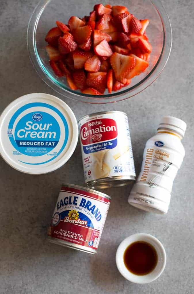 Ingredients for making Fresas con crema including containers of sour cream, sweetened condensed milk, evaporated milk, whipping cream, a bowl of sliced strawberries and vanilla extract.
