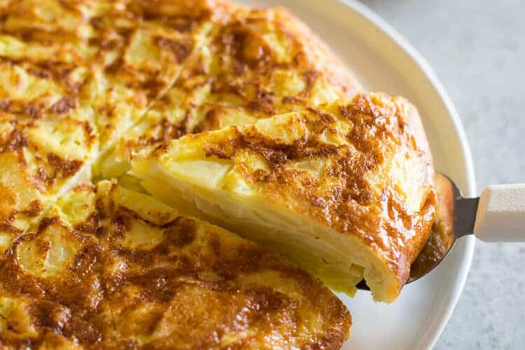 Spanish tortilla de patata on a plate with a slice being served and a baguette and salad in the background.