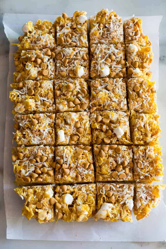 Cereal bars with cornflakes, marshmallows and butterscotch chips cut into squares.