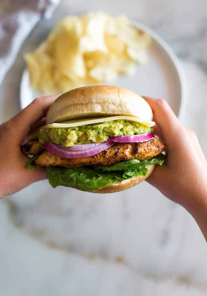 Hands holding the middle of the chicken burger up towards the camera lens, with potato chips on a plate in the background.