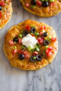 Mexican Pizza made with two corn tortillas with cheese, tomato, olives and sour cream.