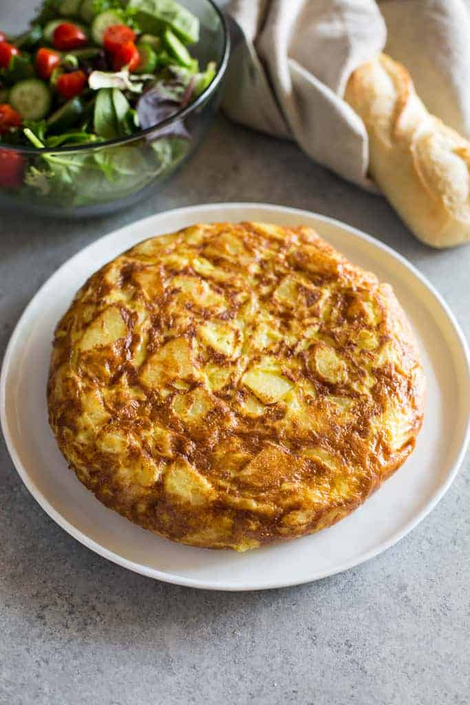 Tortilla de patata on a white plate with salad and a baguette in the background.