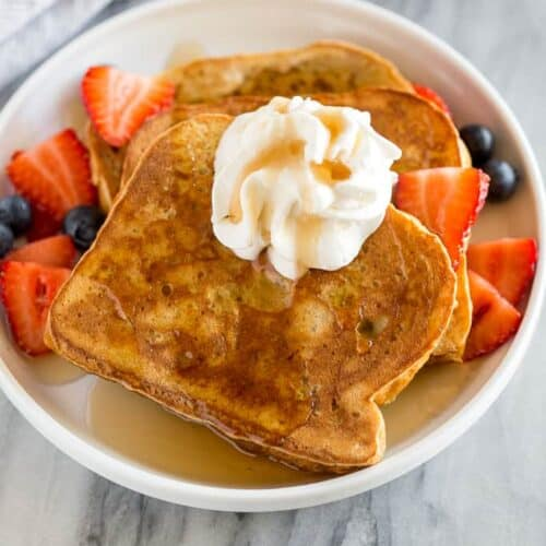 Three slices of Brioche French Toast on a white plate with whipped cream and syrup on top and strawberries and blueberries on the sides.
