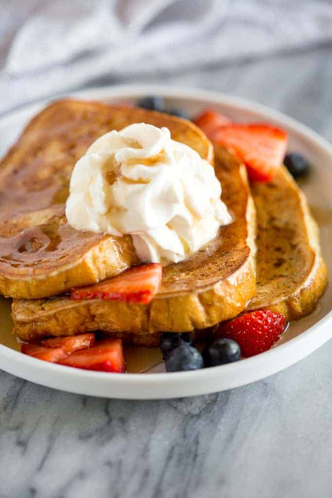Close-up photo of slices of French Toast on a white plate with whipped cream, berries and syrup on top.