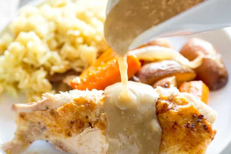 Chicken gravy in a white gravy boat being poured over a chicken breast on a plate with sides of rice and vegetables.