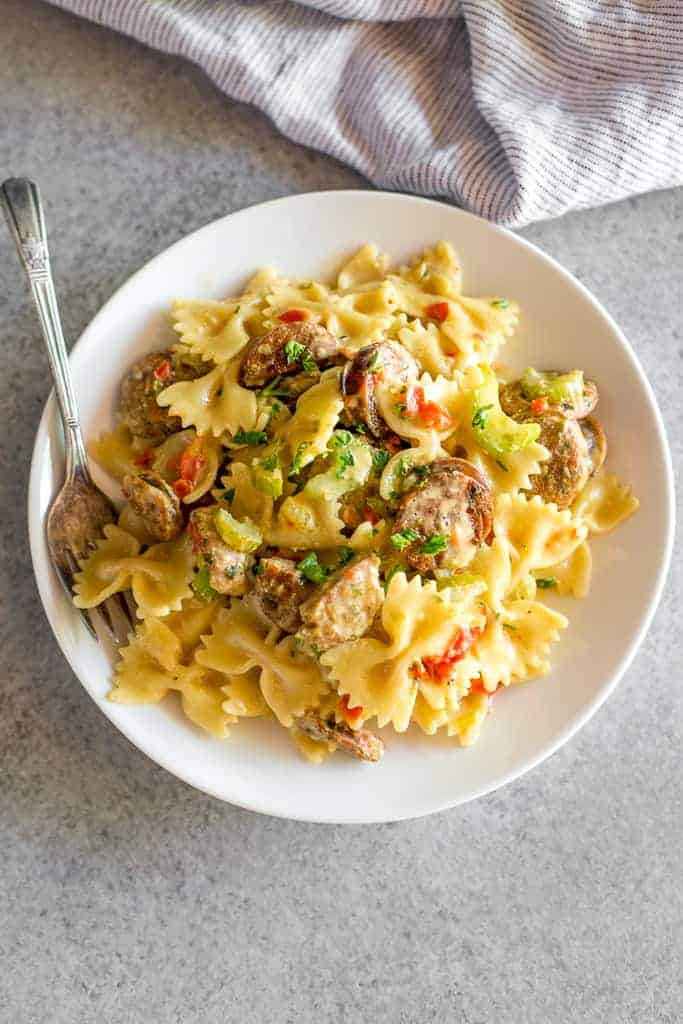 A white bowl with cooked farfalle pasta with sausages and diced red bell pepper in a creamy cajun sauce, with a fork in the bowl.