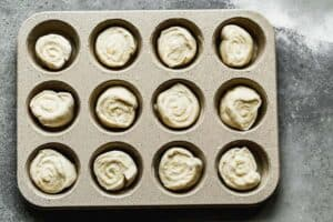 Rolled orange rolls dough in muffin tin ready to bake.
