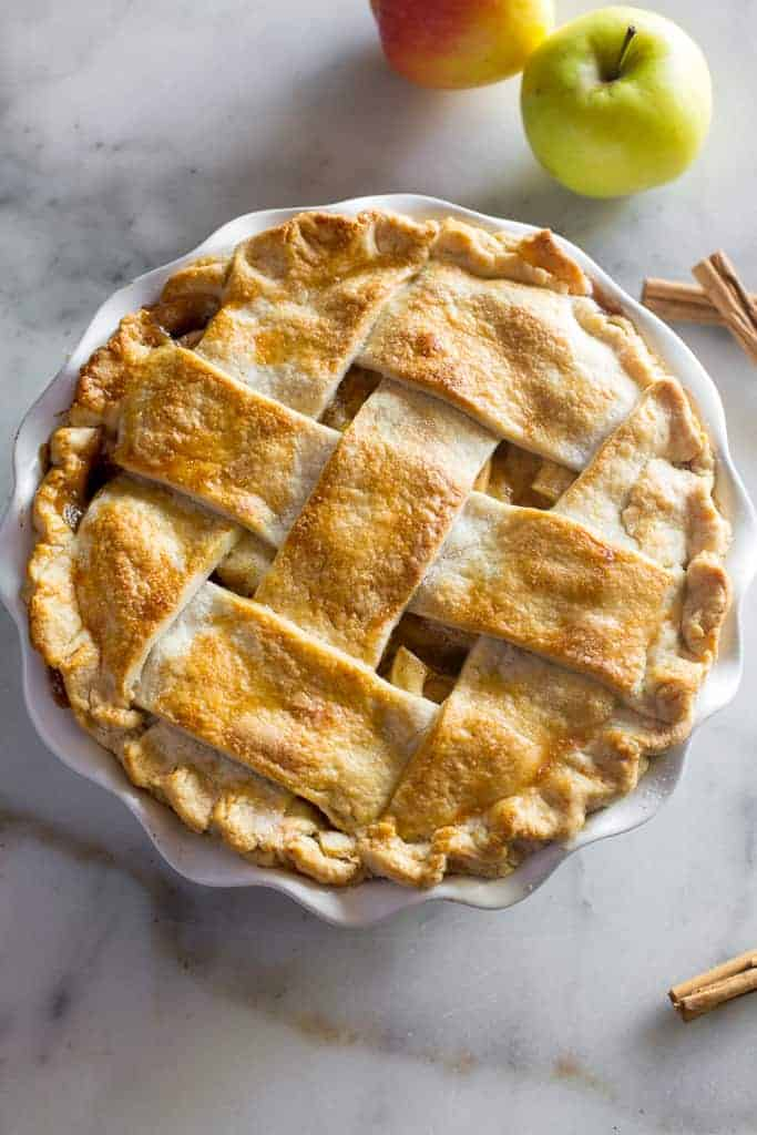 Overhead photo of a baked apple pie with a lattice crust and apples and cinnamon sticks in the background.
