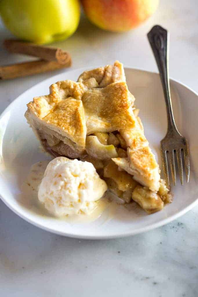A slice of apple pie on a plate with a scoop of ice cream and a fork.
