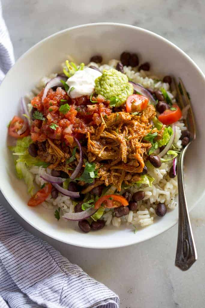 A white bowl with rice, black beans, sweet pork, salsa, guacamole and sour cream.