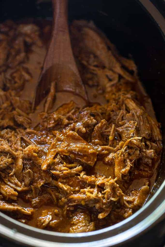 A crock pot full of shredded sweet pork in a red sauce, with a wooden spoon in the slow cooker to serve the meat.