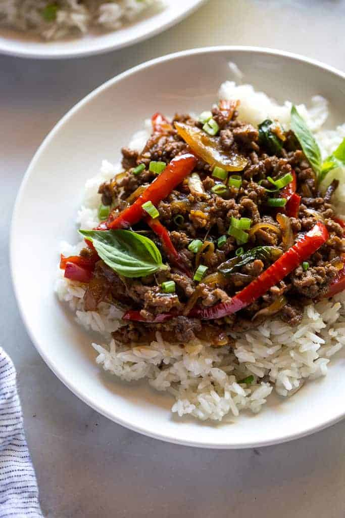 Close-up of Thai basil beef over white rice, on a white plate, on a white marble board.