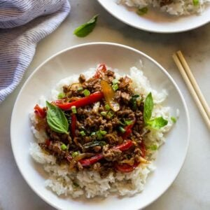 A white plate with white rice and Thai basil beef on it, chopsticks on the side and another plate of food behind it.