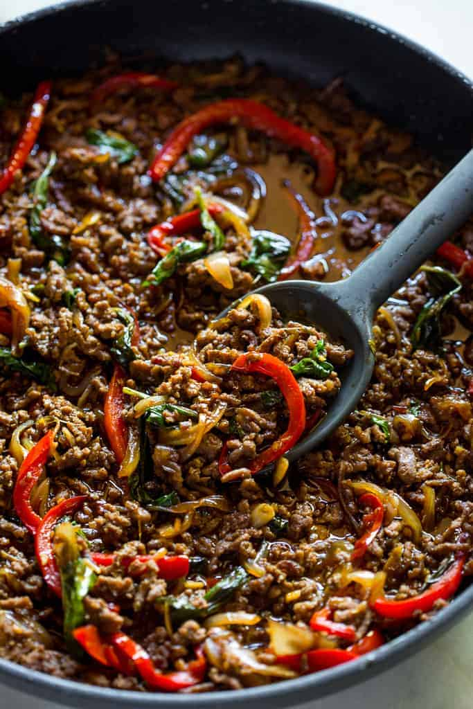 A skillet with Thai Basil Beef made with ground beef, red bell pepper, onion and basil.