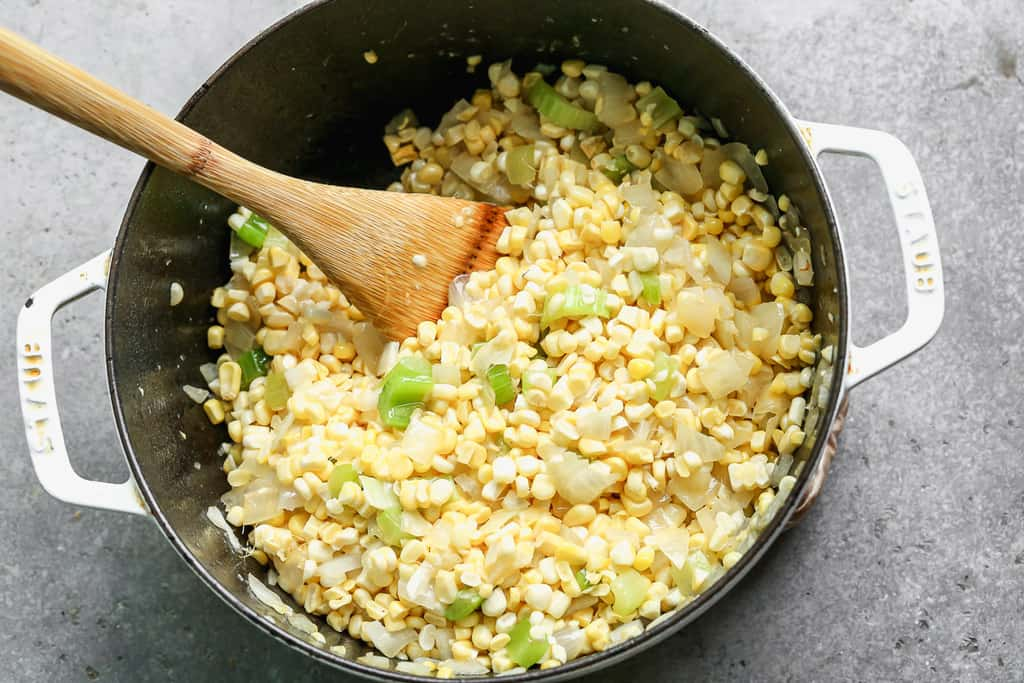 Fresh corn kernels added to a large pot with sautéed celery and onion, to make corn chowder.