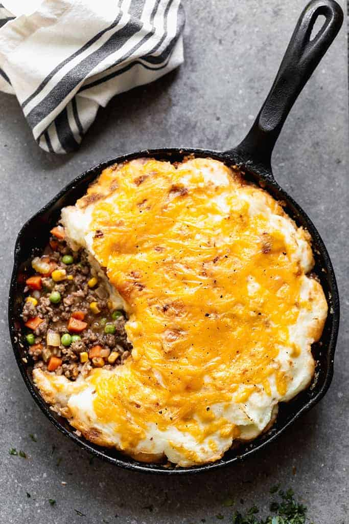 Overhead photo of a cast iron pan with baked cottage pie consisting of a meat and vegetable gravy mixture topped with mashed potatoes and melted cheddar cheese.