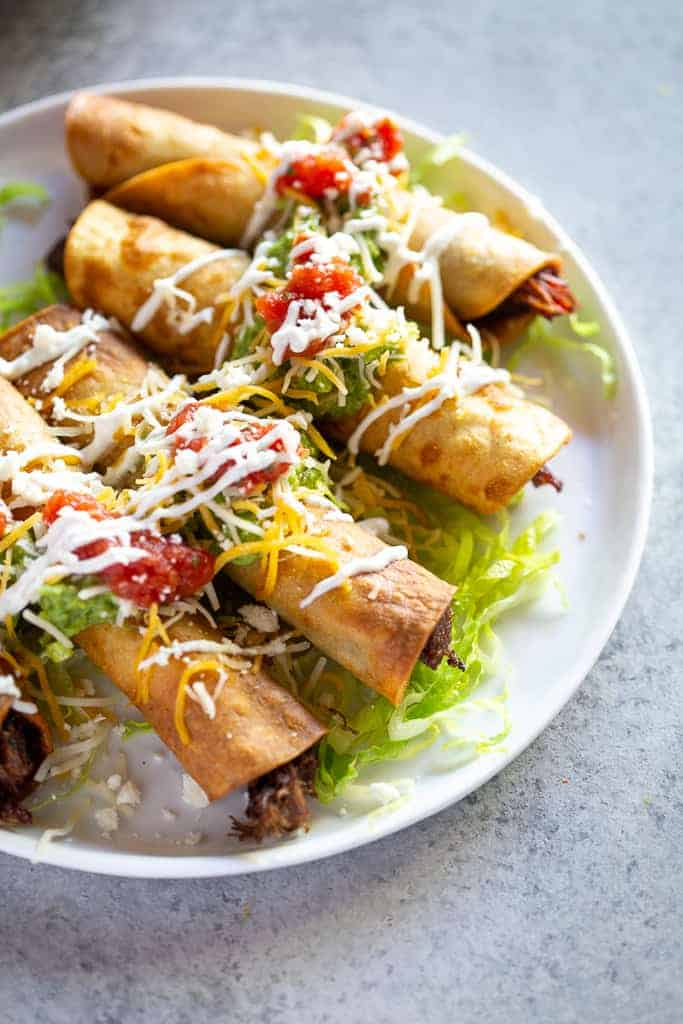 Close-up photo of taquitos on a plate, topped with guacamole, cheese, sour cream and salsa.