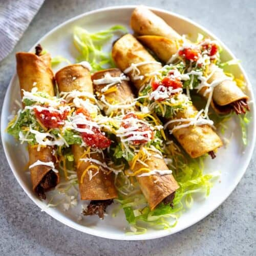 Five beef taquitos fanned out on a plate topped with guacamole, sour cream and salsa.