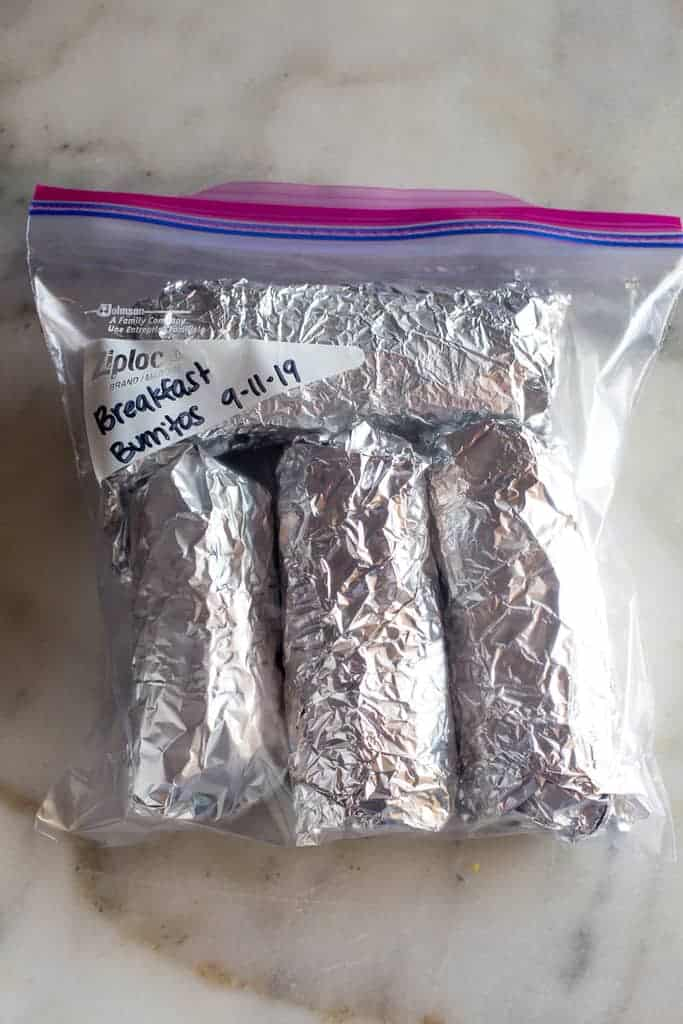 Frozen breakfast burritos wrapped in tinfoil in a labeled ziplock bag.