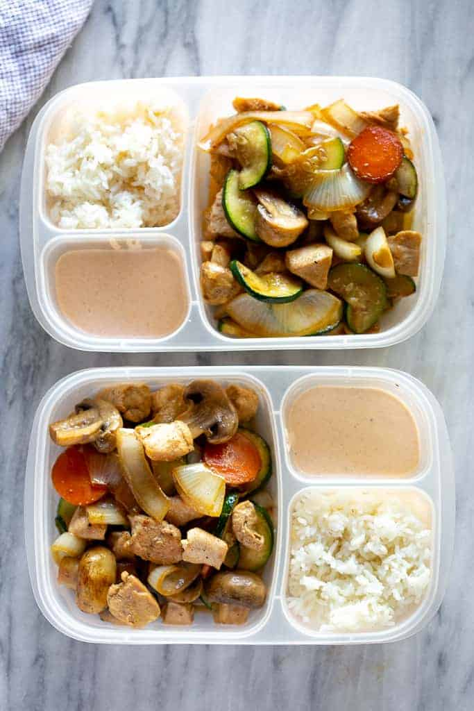 Meal prepped hibachi chicken in containers with rice and sauce.