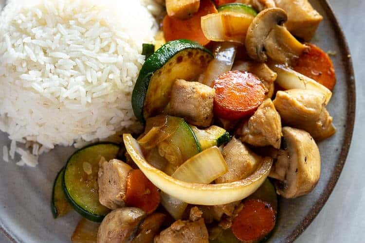 Hibachi chicken stir-fry with a side of rice and yum yum sauce in the background.