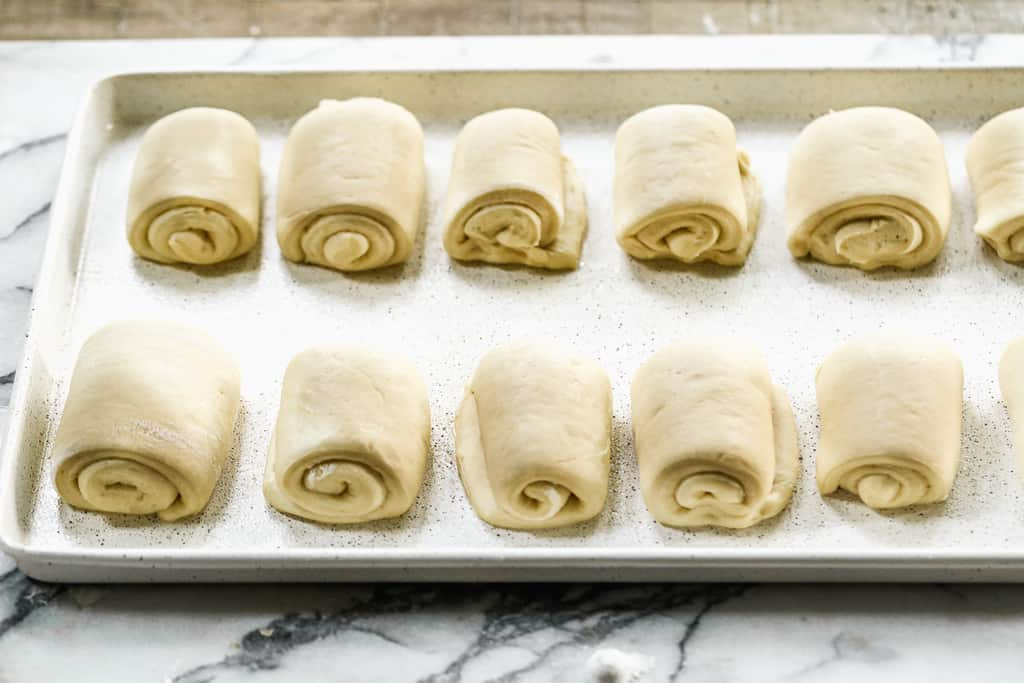 A sheet pan with risen dinner roll dough rolls ready to bake.