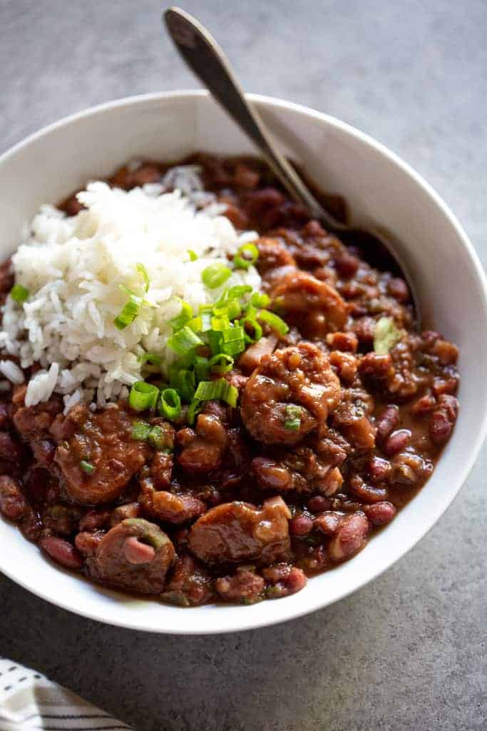 Close up of a white bowl with red beans and rice topped with white rice and chopped green onion.