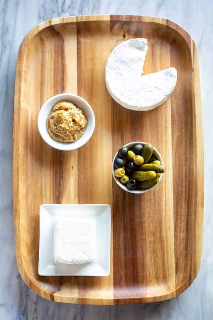 A wood serving board with a bowl of mustard, bowl of olives, brie cheese and plate with cream cheese.