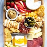 Charcuterie board with meats, sliced cheese, dips, crackers and fruit, served on a wood board.