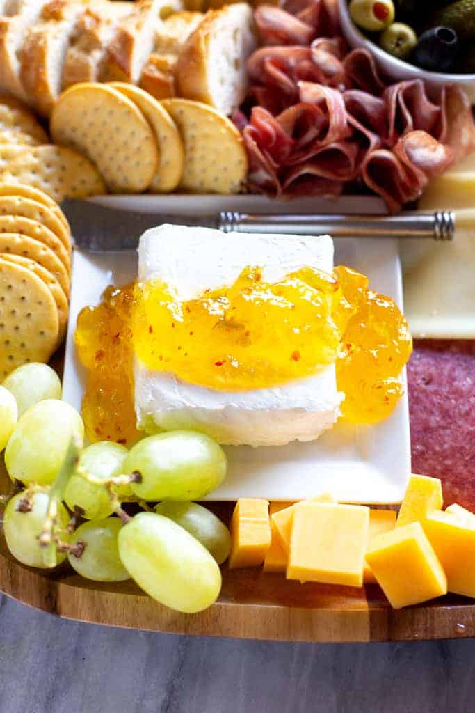 Cream cheese with jalapeño jelly on top and crackers, cheese, grapes and cured meat on the sides.
