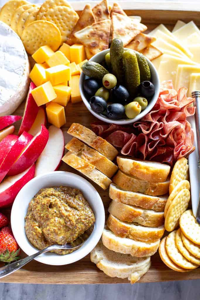 A section of a charcuterie board with sliced baguettes, apples, cheese and a bowl with olives.