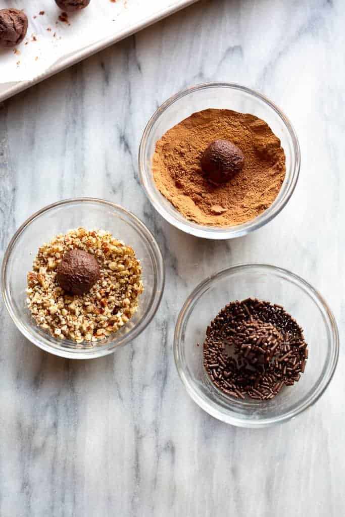 Three bowls with chocolate truffle toppings including crushed pecans, cocoa powder, and sprinkles.