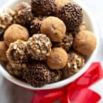 A bowl of chocolate truffles coated with cocoa powder, chopped nuts and chocolate sprinkles.