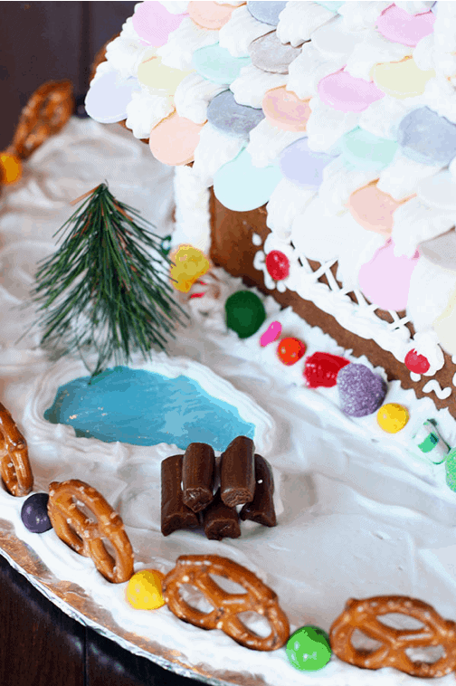 A pretend lake and log pile on the side of a gingerbread house.