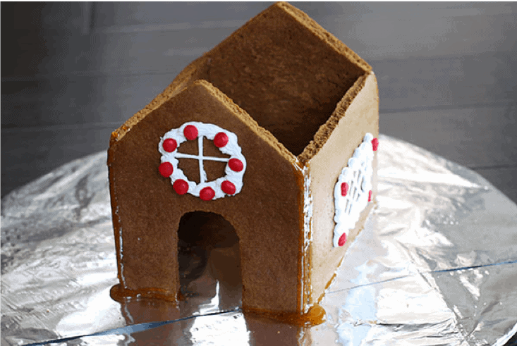 The base of a gingerbread house assembled on a board.
