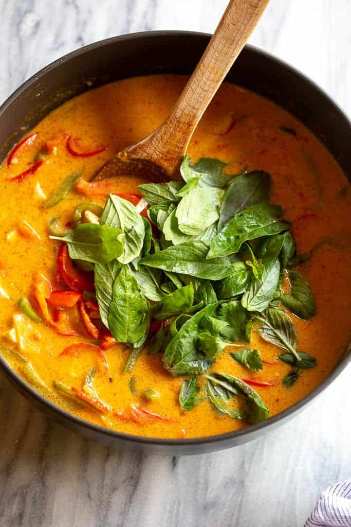 A pot of panang curry with fresh basil leaves on top.