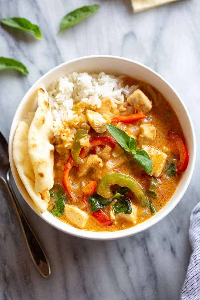Panang Curry in a bowl with white rice and naan bread.