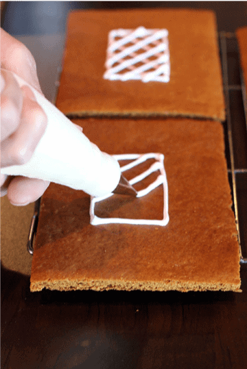 The sides of a gingerbread house being decorated with frosting.