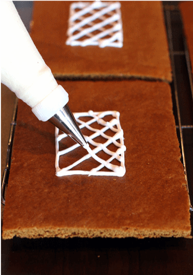A window being drawn with frosting on a rectangle piece of gingerbread.