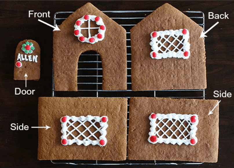 The pieces of a homemade gingerbread house laid out on a wire cooling rack.