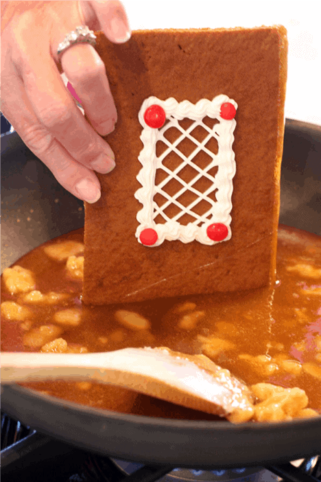 A side of a gingerbread house dipping in melted sugar.