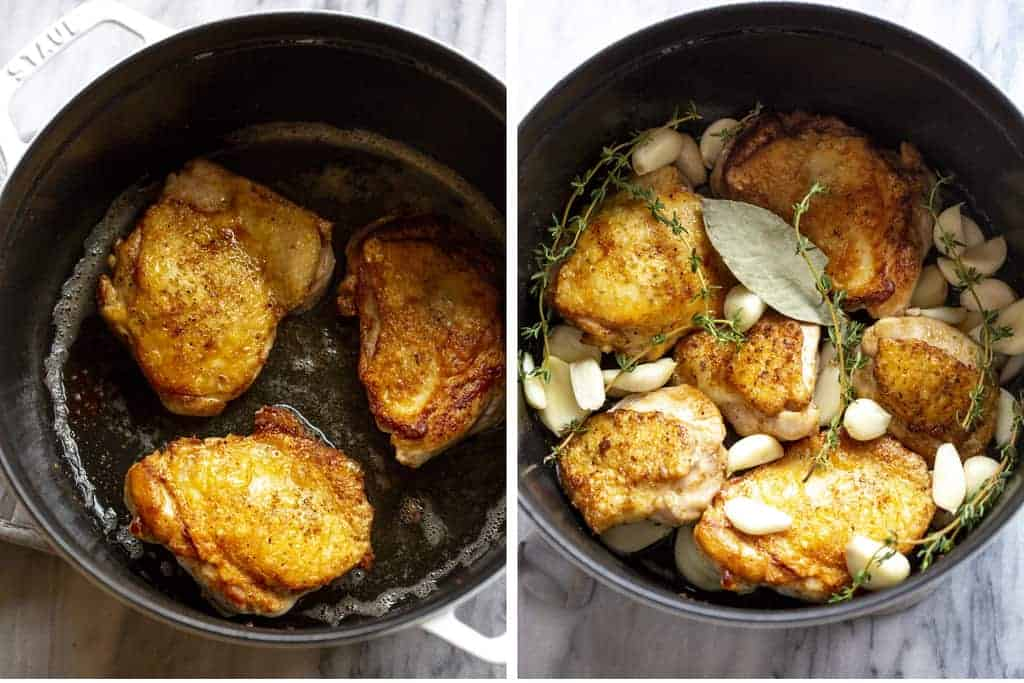 Browned chicken thighs in a cast iron pot and then garlic cloves, bay leaves and thyme sprigs added to the pot.