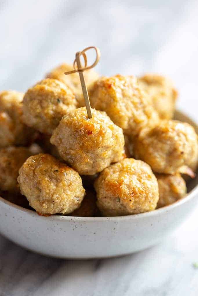 A bowl of baked chicken meatballs with a toothpick in one.