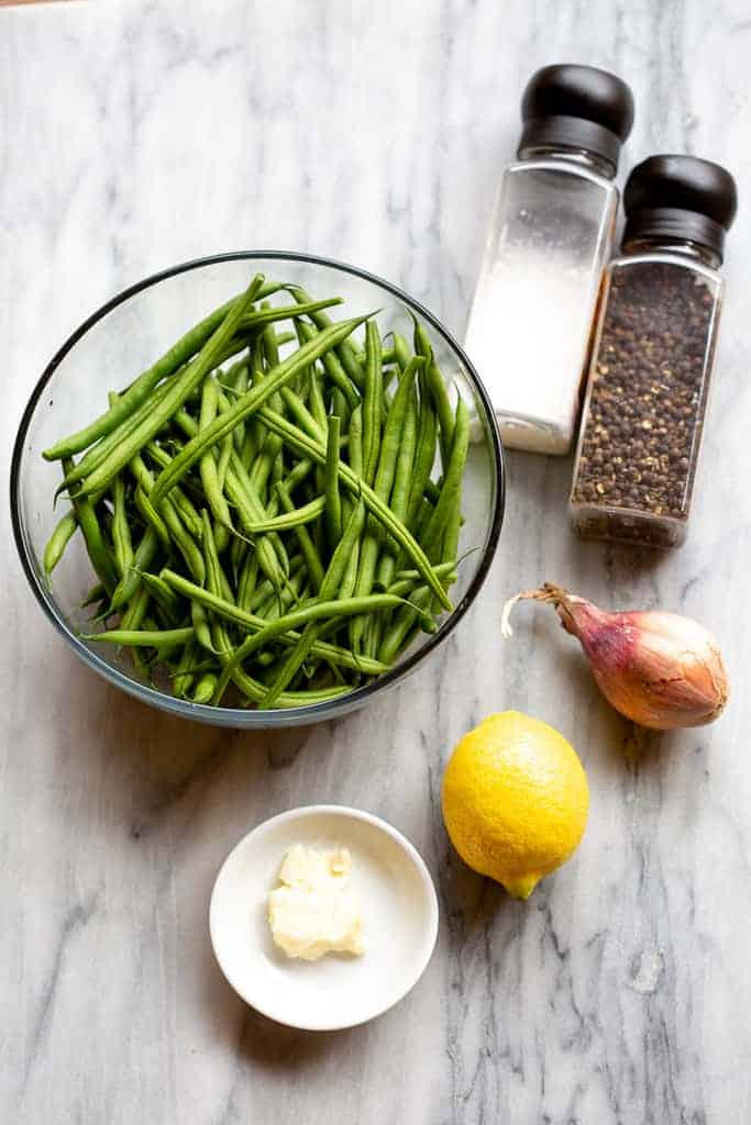 French green beans in a bowl next to salt and pepper, shallot, onion, lemon and butter.