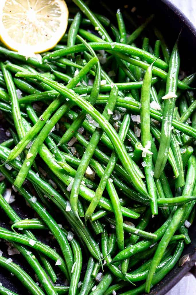 Close-up photo of cooked french green beans in a skillet.