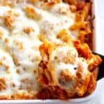 A white casserole dish with ziti pasta, meatballs and cheese lifted out with a spoon.
