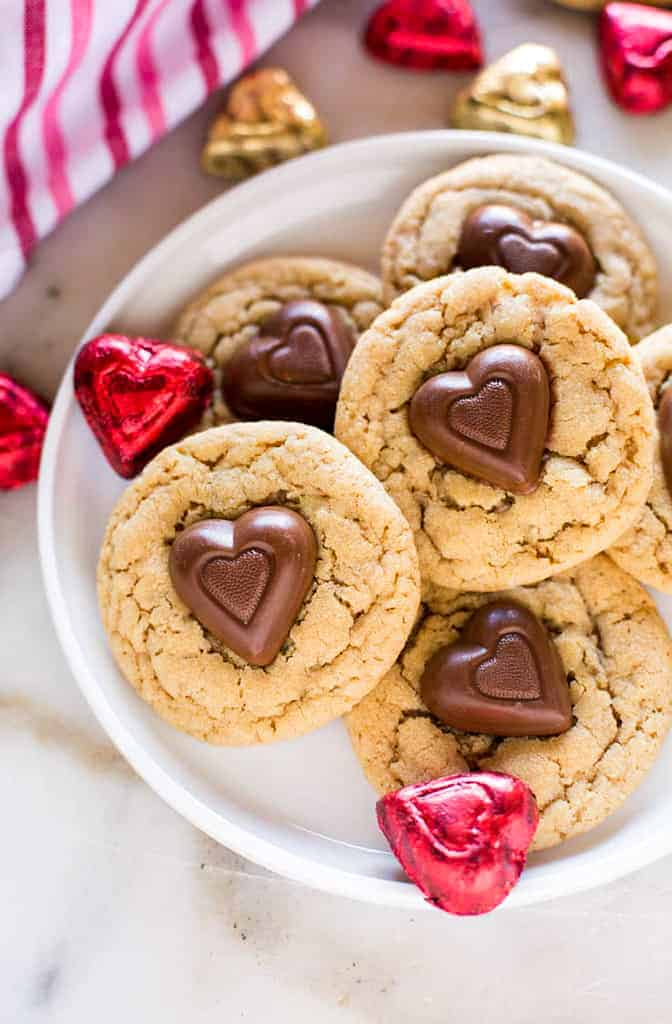 Peanut Butter Cookies with a reese's chocolate heart in the center, stacked on a plate.