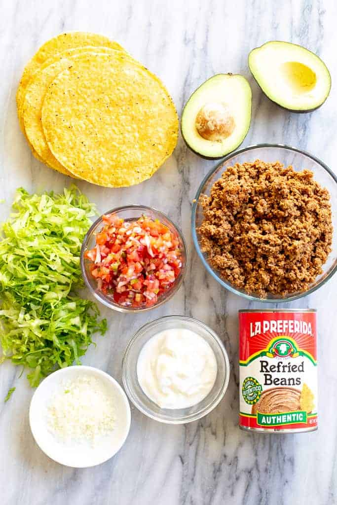 Tostada ingredients including shells, ground beef, shredded lettuce, pico de gallo, sour cream, a can or refried beans and an avocado.